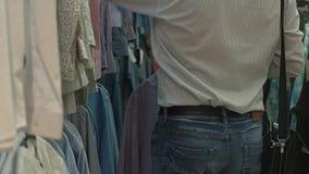 De mens kiest een overhemd in de wandelgalerij Langzame Motie stock footage