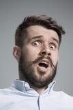 De mens kijkt doen schrikken Over grijze achtergrond Royalty-vrije Stock Foto