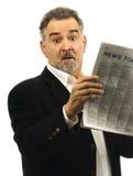 De mens kijkt geschokt terwijl het lezen van krant royalty-vrije stock foto's