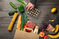 De mens kijkt het hoogtepunt van de pakpapierzak van verschillend gezond voedsel stock foto's