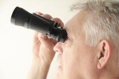 De mens kijkt omhoog met verrekijkers Stock Foto's