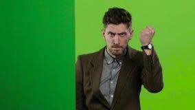 De mens kijkt uit van achter een groene raad en schreeuwt een Het groene scherm Langzame Motie stock videobeelden