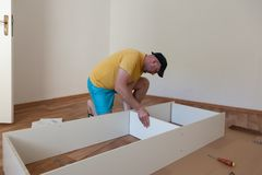 De mens kleedde toevallig het assembleren meubilair in nieuw huis Timmerman reparatie en het assembleren meubilair thuis stock afbeelding