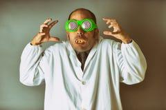 De mens kleedde zich als gekke wetenschapper met een laboratoriumlaag, gekke glazen, en vampiertanden stock afbeelding