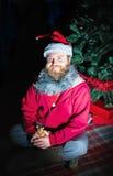 De mens kleedde zich als Santa Sitting Under The Christmas-Boom Royalty-vrije Stock Afbeelding
