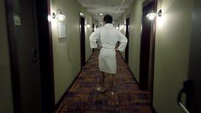 De mens kleedde zich in een badjas en pantoffels lopend bij de lange hotelgang stock videobeelden
