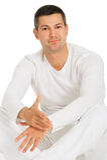 De mens kleedde zich in witte zitting op de vloer Royalty-vrije Stock Fotografie