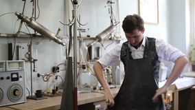 De mens kleedt de laboratoriumlaag vóór de chemische experimenten stock videobeelden