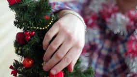De mens kleedt mooi weinig gloeiende Kerstboom stock footage