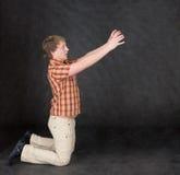 De mens knielt en rekhanden aan iets Stock Foto's