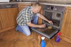 De mens knielt op de vloer in de keuken en maakt de oven schoon Stock Fotografie
