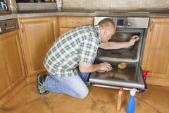 De mens knielt op de vloer in de keuken en maakt de oven schoon Stock Foto