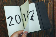 De mens knipt blocnoteblad op een houten lijst weg 2016 draait, opent 2017 bovenkant Stock Foto