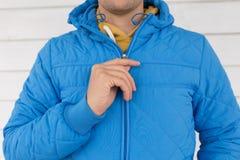 De mens knoopt blauw gewatteerd jasje dicht royalty-vrije stock foto's
