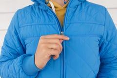 De mens knoopt blauw gewatteerd jasje dicht stock foto's
