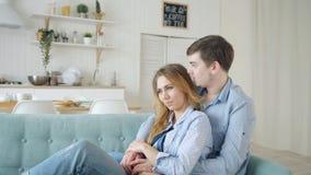 De mens koestert damezitting op bank en het kussen in keuken stock videobeelden