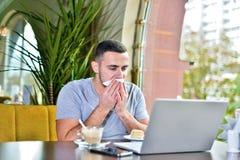De mens in de koffie at en veegt zijn mond met servet af stock foto