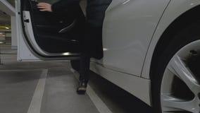 De mens komt aan een auto binnen in een garage wordt geparkeerd die stock video
