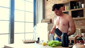 De mens kookt een eiwitcocktail in de keuken stock videobeelden