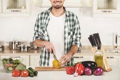 De mens kookt plantaardige salade in de keuken stock fotografie