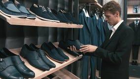 De mens koopt klassieke kleren en schoenen stock videobeelden