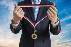 De mens in kostuum geeft gouden medaille Verschillende 3d bal Stock Afbeeldingen