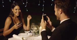 De mens in kostuum neemt foto van mooie dinerdatum stock videobeelden