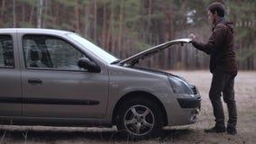 De mens krijgt uit de auto en opent de kap stock videobeelden