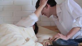 De mens kust een slaapmeisje en zij ontwaakt stock footage