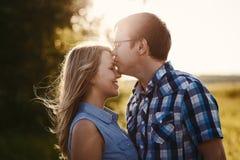 De mens kust het meisje op het voorhoofd bij zonsondergang in de zomer royalty-vrije stock foto's