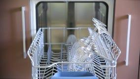 De mens laadt het dienblad met de schotels en sluit de afwasmachinedeur stock footage
