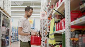 De mens leert een rode plastic bus voor auto in een winkel stock footage