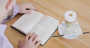 De mens leest een boek met zijn vinger op de paginazitting in koffie met kop van cappuccino Snelheidslezing stock videobeelden