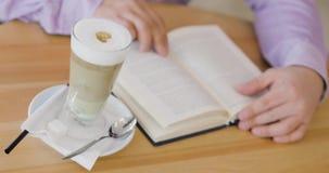 De mens leest een boekzitting in koffie met kop van cappuccino stock video