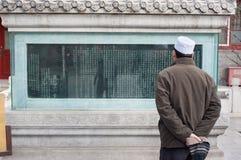 De mens leest een inschrijving op een oude stele bij Niujie-Moskee, Peking, China Royalty-vrije Stock Foto's