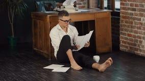 De mens leest Pagina's op Vloer stock videobeelden