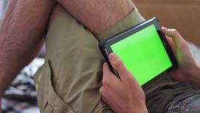 De mens legt op Laag thuis en Horloge op Tablet met het Groene Scherm stock video