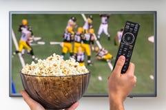 De mens let rugby op gelijke op TV Stock Foto's