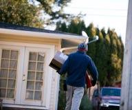 De mens levert pakketdoos aan huis op leveringsadres Stock Afbeeldingen