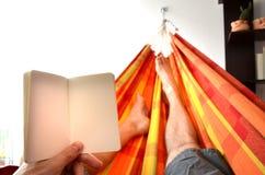 De mens ligt in binnenhangmat en kijkt aan leeg berichtboek Stock Fotografie