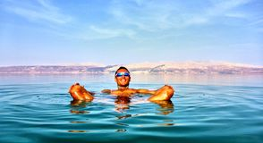 De mens ligt in het dode overzees Jordanië op een achtergrond stock foto's