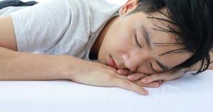 De mens ligt naar voren gebogen op bed, hij in pyjama's in slaapkamer stock video