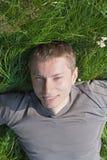 De mens ligt op het gras Royalty-vrije Stock Afbeeldingen