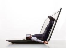 De mens ligt op laptop Stock Foto's