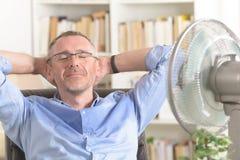De mens lijdt aan hitte in het bureau of thuis stock afbeeldingen