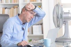 De mens lijdt aan hitte in het bureau of thuis stock foto
