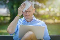 De mens lijdt aan hitte terwijl het werken met laptop stock foto's