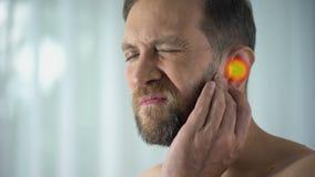 De mens lijdt aan oorpijn, otitis, het horen problemen, wijst de vlek op pijn, close-up stock videobeelden