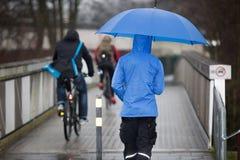 De mens loopt in de regen met zijn paraplu en regenjas over een brug Royalty-vrije Stock Foto's