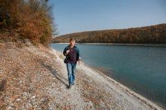 De mens loopt dichtbij meer in de herfst stock afbeelding